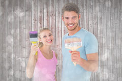 Samengesteld beeld van jong paar die en penselen glimlachen houden Royalty-vrije Stock Foto's