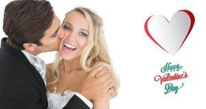 Samengesteld beeld van knappe bruidegom die zijn vrouw op haar wang kussen Royalty-vrije Stock Foto's