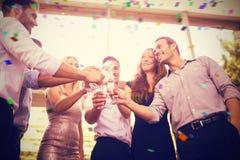Samengesteld beeld van lage hoekmening van vrienden die glazen champagne roosteren stock foto's