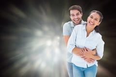 Samengesteld beeld van leuk paar die en bij camera koesteren glimlachen Stock Fotografie