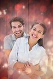 Samengesteld beeld van leuk paar die en bij camera koesteren glimlachen Stock Afbeelding
