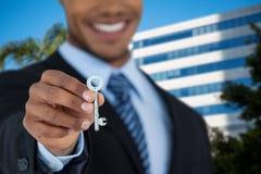 Samengesteld beeld van medio sectie die van zakenman nieuw huissleutel tonen Stock Foto's
