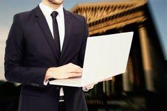 Samengesteld beeld van medio sectie van een zakenman die laptop met behulp van Royalty-vrije Stock Foto's