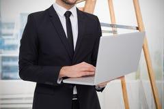 Samengesteld beeld van medio sectie van een zakenman die laptop met behulp van Stock Foto's