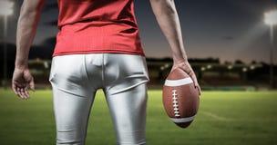 Samengesteld beeld van medio sectie van sportman met Amerikaanse voetbal Stock Afbeeldingen