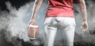 Samengesteld beeld van medio sectie van sportman met Amerikaanse voetbal Stock Foto