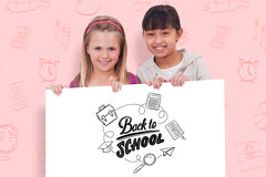 Samengesteld beeld van meisjes achter een leeg paneel Stock Afbeeldingen