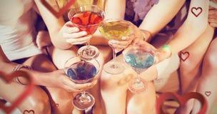 Samengesteld beeld van meisjes met cocktails het roosteren Stock Foto