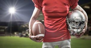 Samengesteld beeld van midsection van de de Amerikaanse helm en bal van de voetbalsterholding Stock Fotografie