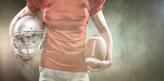 Samengesteld beeld van midsection van de de Amerikaanse helm en bal van de voetbalsterholding Royalty-vrije Stock Foto