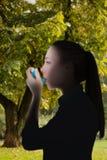 Samengesteld beeld van mooi blonde die een astmainhaleertoestel met behulp van Royalty-vrije Stock Fotografie