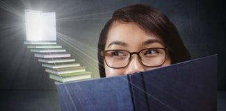 Samengesteld beeld van mooi studenten verbergend gezicht achter een boek Stock Foto's
