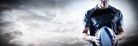 Samengesteld beeld van nadenkende de holdingsbal van de rugbyspeler stock afbeeldingen