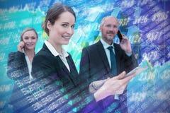 Samengesteld beeld van onderneemster die tablet gebruiken terwijl collega's die op telefoon op achtergrond spreken royalty-vrije stock afbeelding