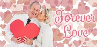Samengesteld beeld van ouder hartelijk paar die rode hartvorm houden royalty-vrije stock afbeeldingen