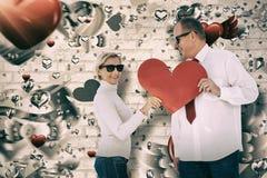 Samengesteld beeld van ouder hartelijk paar die rode hartvorm houden royalty-vrije stock fotografie