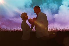 Samengesteld beeld van ouder hartelijk paar die roze hartvorm houden royalty-vrije stock afbeelding