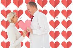 Samengesteld beeld van ouder hartelijk paar die roze hartvorm houden stock fotografie