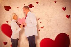 Samengesteld beeld van ouder hartelijk paar die roze hartvorm houden stock afbeelding