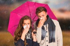 Samengesteld beeld van paar blazende neus terwijl het houden van paraplu stock foto's
