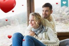 Samengesteld beeld van paar in de winterslijtage die uit door cabinevenster kijken Royalty-vrije Stock Fotografie