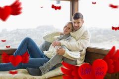 Samengesteld beeld van paar in de zitting van de de winterkleding tegen cabinevenster Royalty-vrije Stock Fotografie