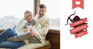 Samengesteld beeld van paar in de zitting van de de winterkleding tegen cabinevenster Royalty-vrije Stock Foto's