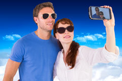 Samengesteld beeld van paar die camera voor beeld met behulp van Royalty-vrije Stock Foto's