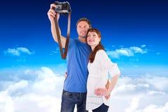 Samengesteld beeld van paar die camera voor beeld met behulp van Stock Afbeelding