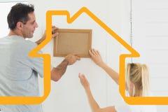 Samengesteld beeld van paar die hun nieuw huis verfraaien Stock Foto