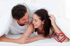 Samengesteld beeld van paar die samen en op bed liggen spreken Royalty-vrije Stock Afbeelding