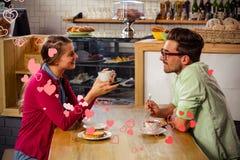 Samengesteld beeld van paar het drinken koffie en 3d valentijnskaartenharten Stock Afbeelding