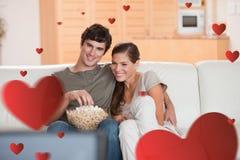 Samengesteld beeld van paar met popcorn op de bank die op een film letten Stock Foto