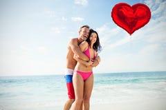 Samengesteld beeld van paar op strand en rode 3d hartballon Stock Afbeeldingen