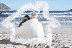 Samengesteld beeld van paarzitting op het strand onder deken die uit aan overzees kijken Stock Foto