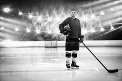 Samengesteld beeld van portret van de holdingshelm en stok van de ijshockeyspeler stock foto's
