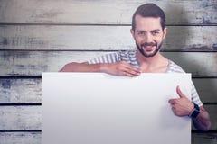 Samengesteld beeld van portret die van de mens duimen tonen terwijl het houden van leeg karton Royalty-vrije Stock Fotografie