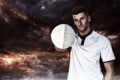 Samengesteld beeld van portret die van rugbyspeler de bal met één hand houden Stock Foto