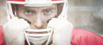 Samengesteld beeld van portret van Amerikaanse voetbalsterholding op zijn helm Stock Foto