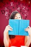 Samengesteld beeld van portret van een student die achter een blauw boek knipogen Royalty-vrije Stock Foto