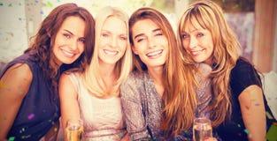 Samengesteld beeld van portret van mooie vrouwen die dranken hebben terwijl het zitten bij bank royalty-vrije stock afbeelding