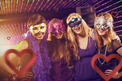 Samengesteld beeld van portret van vrouwelijke vrienden die maskerade in bar dragen royalty-vrije stock foto