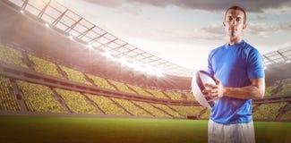 Samengesteld beeld van portret van zekere 3D de holdingsbal van de rugbyspeler Stock Afbeeldingen