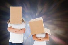 Samengesteld beeld van rijp paar die dozen over hun hoofden dragen Royalty-vrije Stock Afbeeldingen