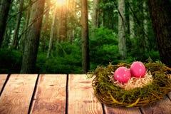 Samengesteld beeld van roze paaseieren op kunstmatig nest Royalty-vrije Stock Afbeelding