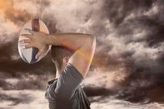 Samengesteld beeld van rugbyspeler die 3D bal werpen Stock Afbeeldingen