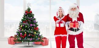 Samengesteld beeld van santa en Mevr. Claus die bij camera glimlachen die gift aanbieden stock afbeeldingen
