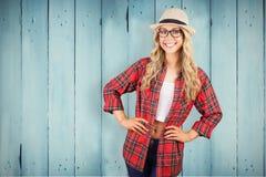 Samengesteld beeld van schitterend blonde die hipster met handen op heupen glimlachen stock foto's