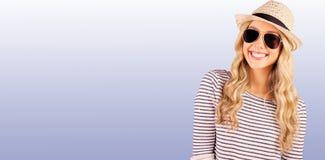 Samengesteld beeld van schitterend glimlachend blonde hipster met zonnebril en strohoed Stock Fotografie