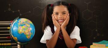 Samengesteld beeld van schoolmeisje die door bol en boeken leunen Stock Foto's